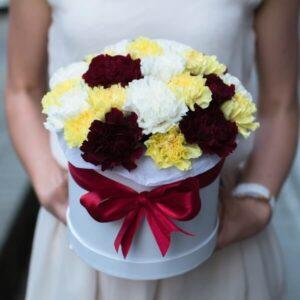 Įvairių spalvų gvazdikai gėlių dėžutėje