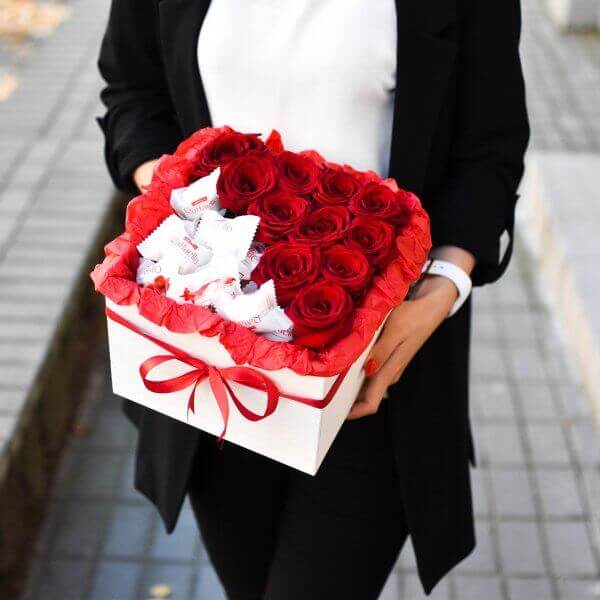 Raudonos rožės ir saldainiai gėlės kvadratinėse dėžutėse